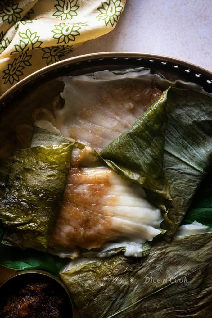 Patholi or kayi genasale are soft rice dumplings steamed in turmeric leaves. Dairy free and glutenfree coastal Karnataka recipe.  These are healthy oil-free, nut free, refined sugar dumplings #glutenfree #vegan #dumplings #steamed #patholi